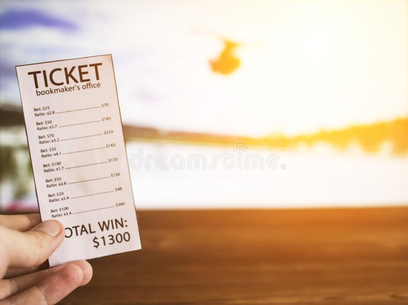 Bookmaker ticket on the background of the TV on which the sport of freestyle shows, sports betting, bookmaker. Bookmaker ticket on the background of the TV on royalty free stock photography