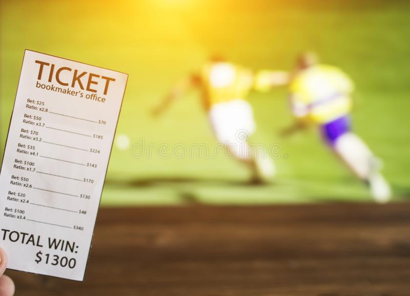 Bookmaker ticket on the background of the TV on which the sport is shown in the game of hurling, sports betting, bookmaker. Bookmaker ticket on the background of stock photo
