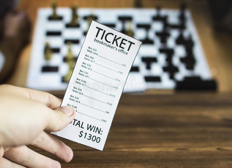 Bookmaker ticket on the background of the TV on which the sport is shown playing chess, checkers, sports betting, chess, bookmaker. Bookmaker ticket on the royalty free stock image