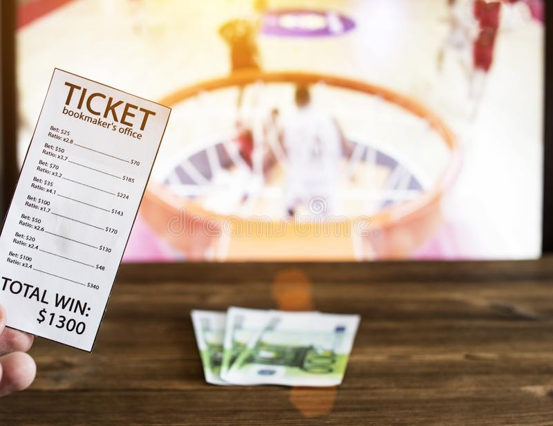 Bookmaker ticket and euro money on the background of a TV on which basketball is shown, bookmaker. Bookmaker ticket and euro money on the background of a TV on royalty free stock photo