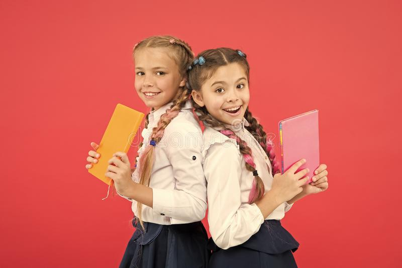 These books are absolutely genius. Genius little children smiling on red background. Happy genius girls or wonder kids royalty free stock images