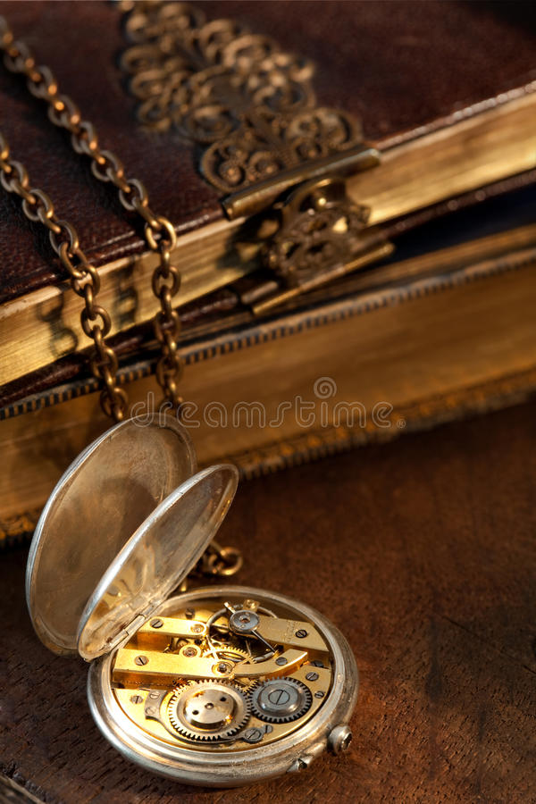 Books and antique pocket watch stock photos