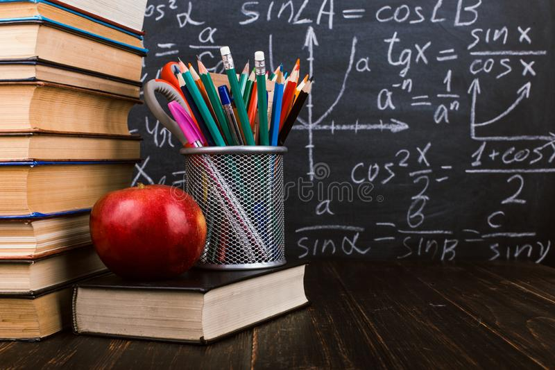 Books, an apple, stand for pens on wooden table, against the background of chalk board with formulas. Teacher`s day concept and stock image