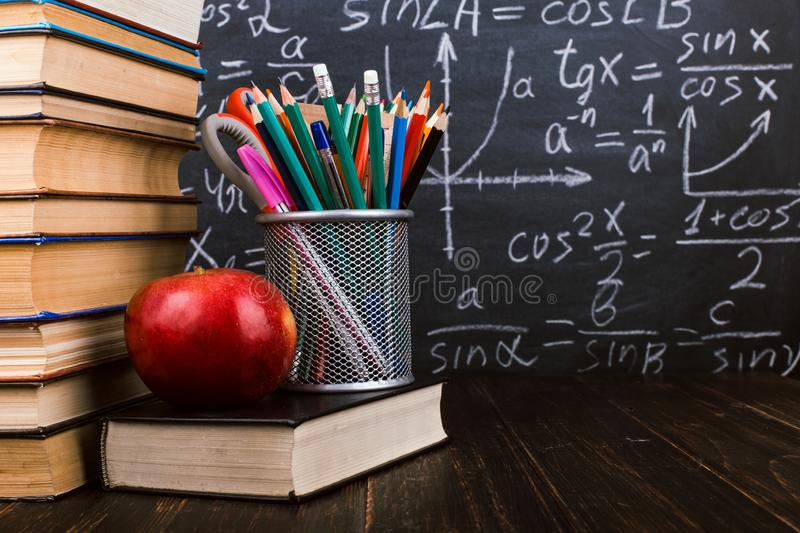 Books, an apple, stand for pens on wooden table, against the background of chalk board with formulas. Teacher`s day concept and stock images