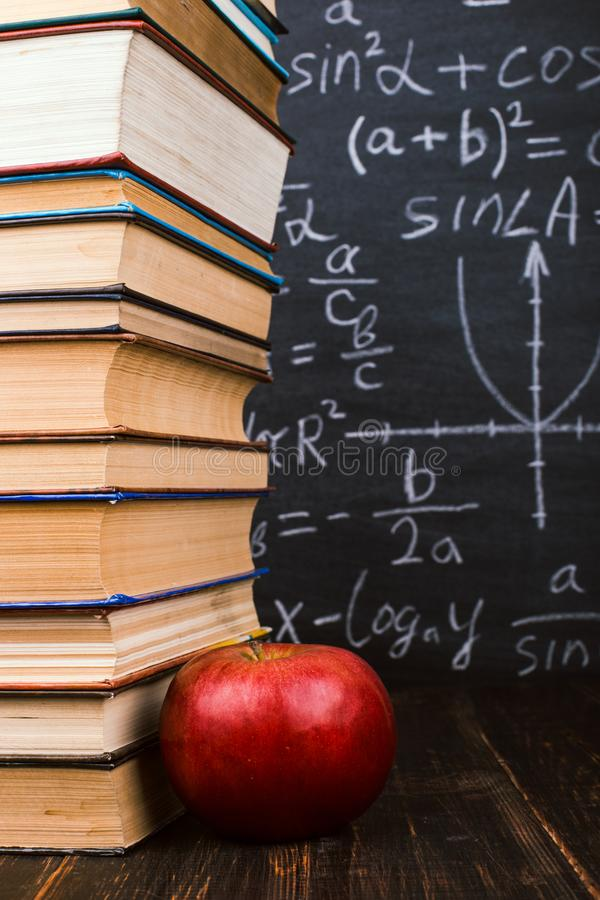 Books and an apple on a wooden table, against the background of a chalkboard with formulas. Teacher's day concept and back to. Books and an apple on wooden stock images
