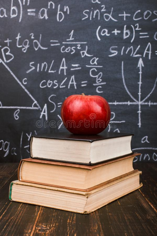 Books and an apple on a wooden table, against the background of a chalkboard with formulas. Teacher& x27;s day concept and back to stock image