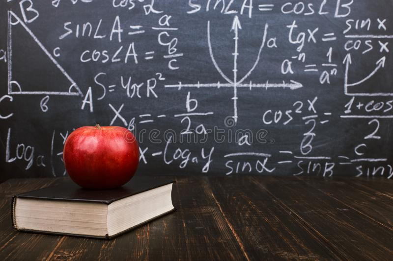 Books and an apple on a wooden table, against the background of a chalkboard with formulas. Teacher's day concept and back to royalty free stock image