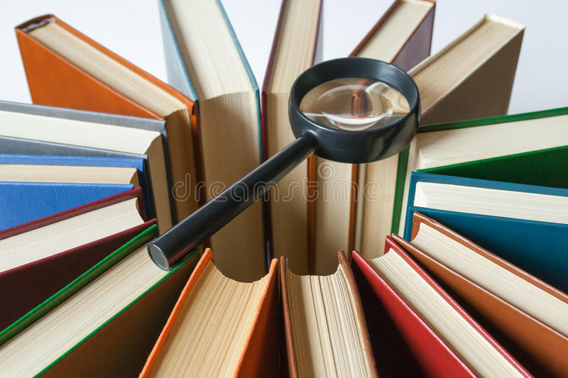Books are arranged in a circle in the center on them lies a magnifying glass (search concept) stock photos