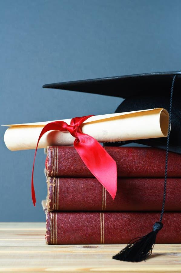 books avläggande av examenmortarboardscrollen royaltyfri fotografi