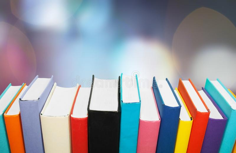 Row of of colorful books on blutted backgtound royalty free stock images
