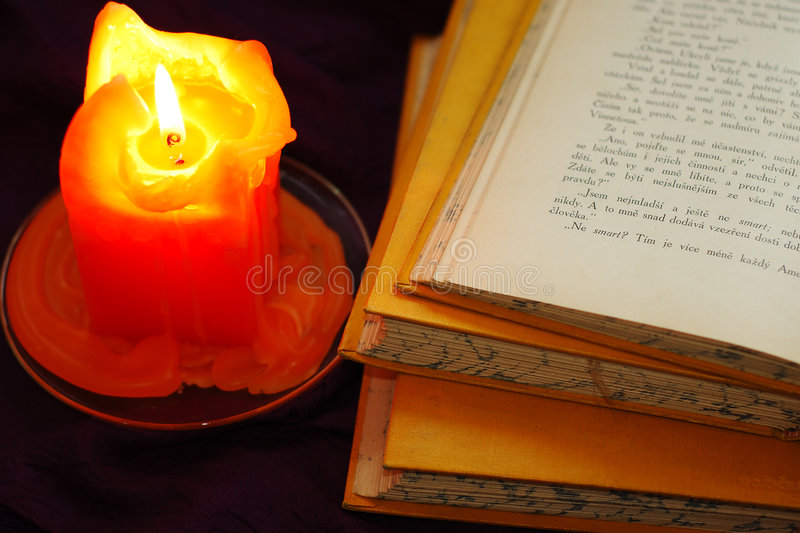 Books with candle. Old open book with candle stock photos