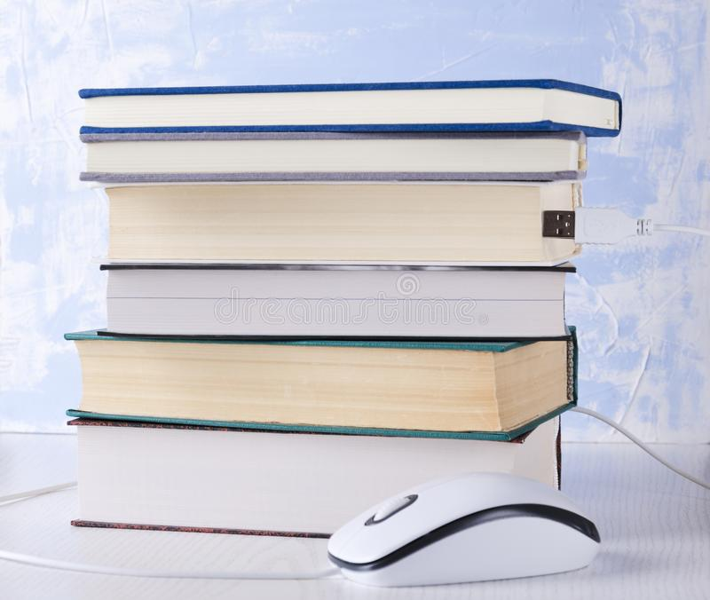 Closeup of stack of books and computer mouse.Concept of e-learning and reading royalty free stock image
