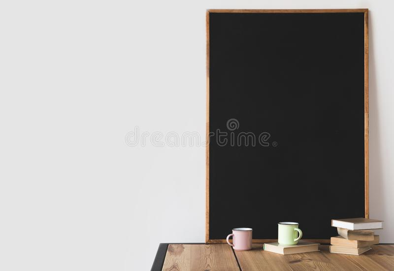 books and cups with big blackboard on wooden table stock photo