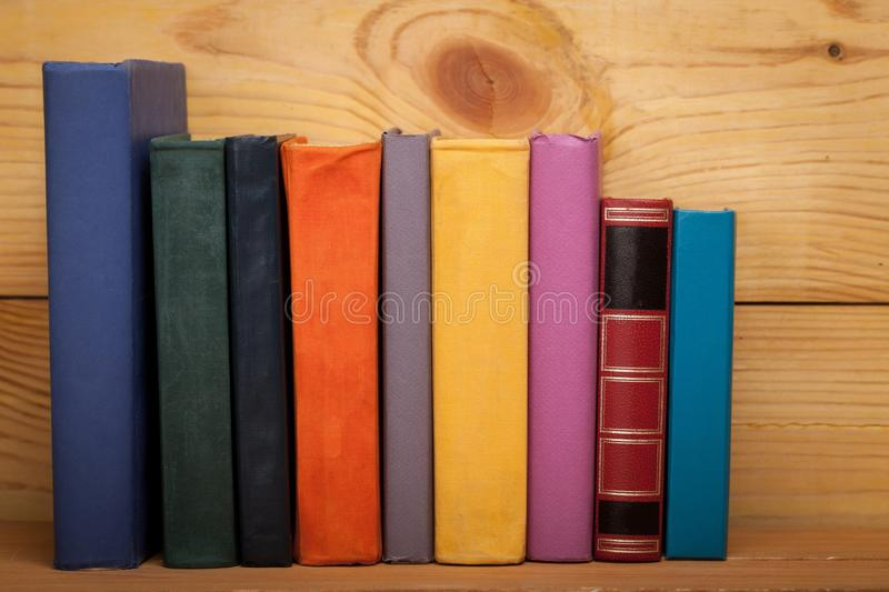 Books of different colors on a wooden shelf. Books erudition studying literature information knowledge education stock image