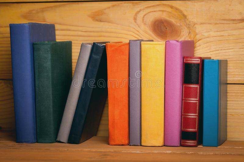 Books of different colors on a wooden shelf. Books erudition studying literature information knowledge education stock photos