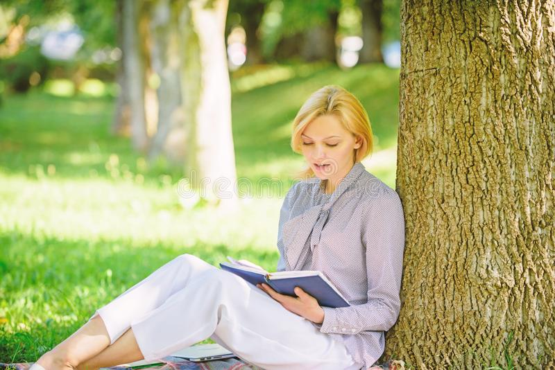 Books every girl should read. Girl concentrated sit park lean tree trunk read book. Reading inspiring books. Bestseller. Top list. Relax leisure an hobby royalty free stock images