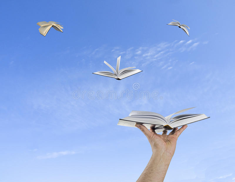 Books flying from hands stock photos