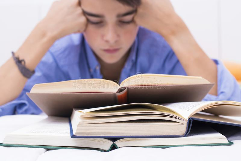Books in the foreground with young people studying. Teaching and education royalty free stock images
