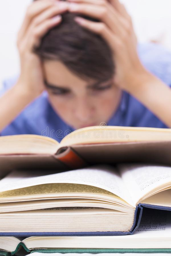 Books in the foreground with young people studying. Teaching and education royalty free stock image