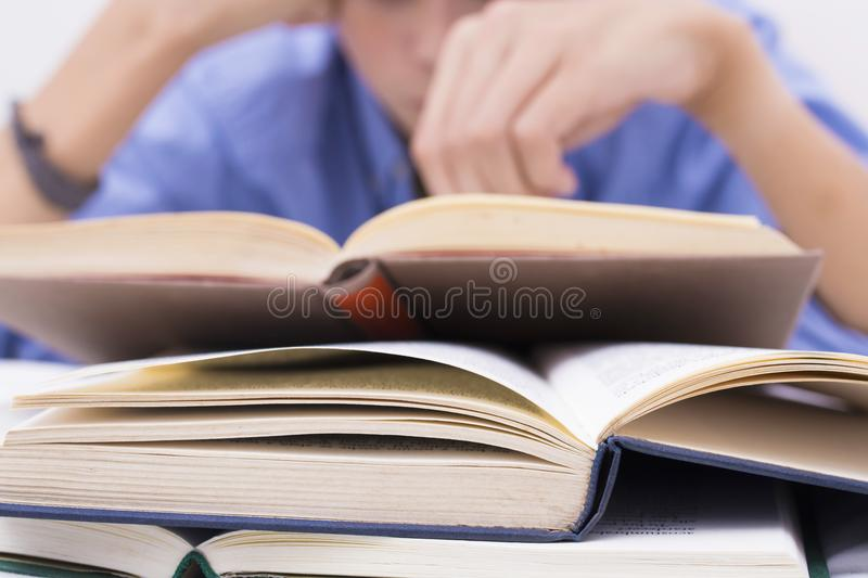 Books in the foreground with young people studying. Teaching and education stock photo