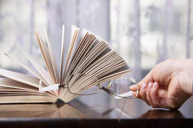 Books and glasses over a wood table stock photo
