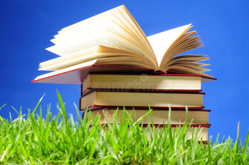 Books on grass. Educational concept. stock images