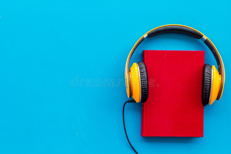 Books with headphones for listening to audiobook on blue background top view copy space royalty free stock images
