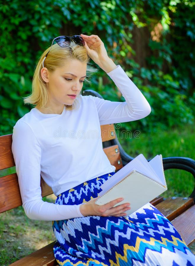 Books are her passion. Woman blonde take break relaxing in park reading book. Girl sit bench relaxing with book, green stock photography