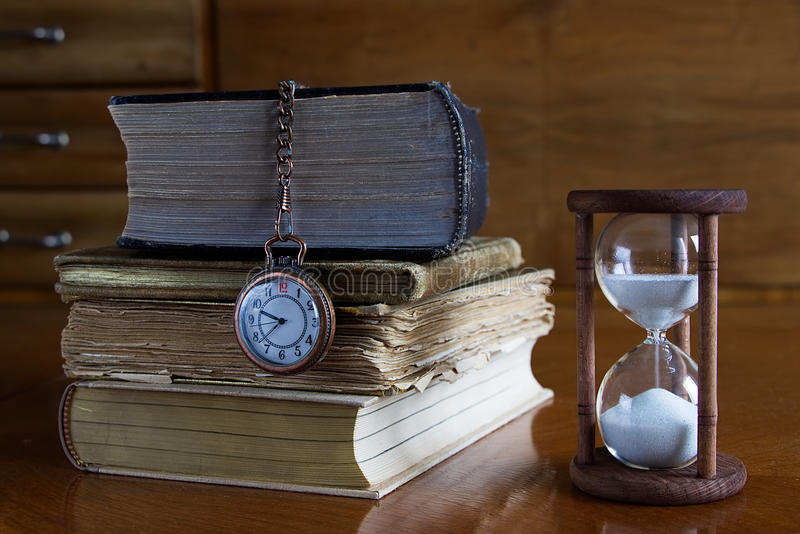 Books with hourglass and pocket clock royalty free stock photos
