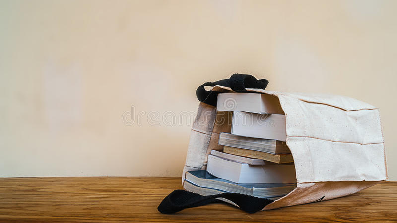 Books inside cloth bag on wood table royalty free stock photo