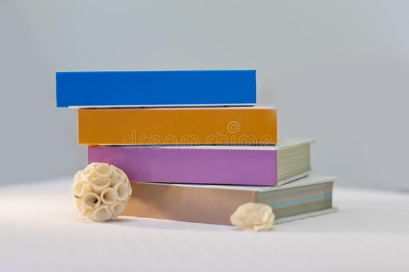 Books layered on the table with empty covers, ideal for mock-ups. With flower decoration royalty free stock photos