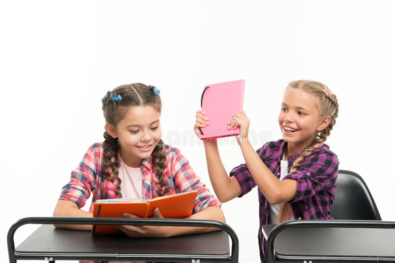 Books are not for hitting. Naughty little girl spoiling her classmate for fighting on books isolated on white. Playful royalty free stock images