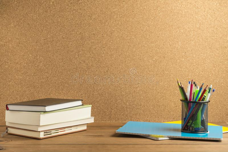 Books, notebooks and school supplies on wooden boards with a cork board in the background royalty free stock photography