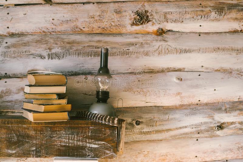 Books and oil lamp on the table. wooden background. vintage. stock images