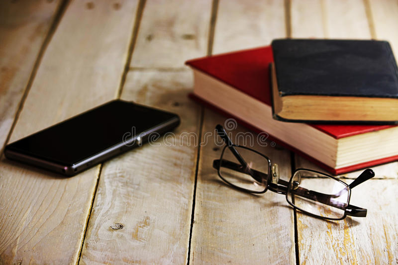 Books on an old wooden surface. Glasses and books on an old wooden surface. Instagram style filter added royalty free stock image