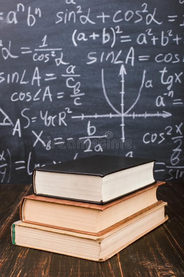 Free Books On A Wooden Table, Against The Background Of A Chalk Board With Formulas. Teacher&x27;s Day Concept And Back To School Stock Photo - 146936950