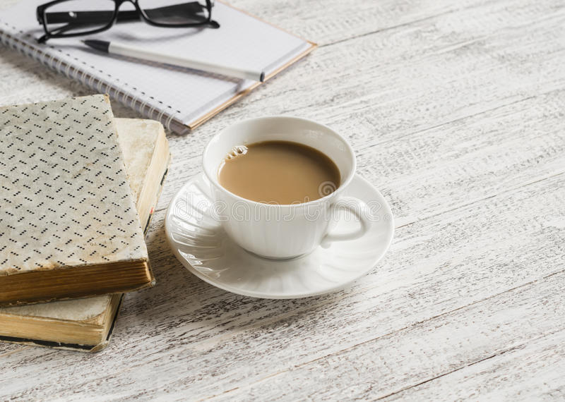 Books, open a blank notepad and a cup of tea with milk stock photos