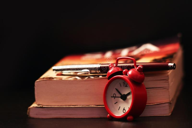 Books pen and clock on the Table stock photo