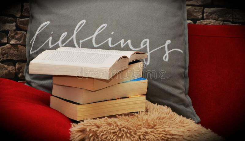 Books pile on a chair and shaggy rug royalty free stock photos