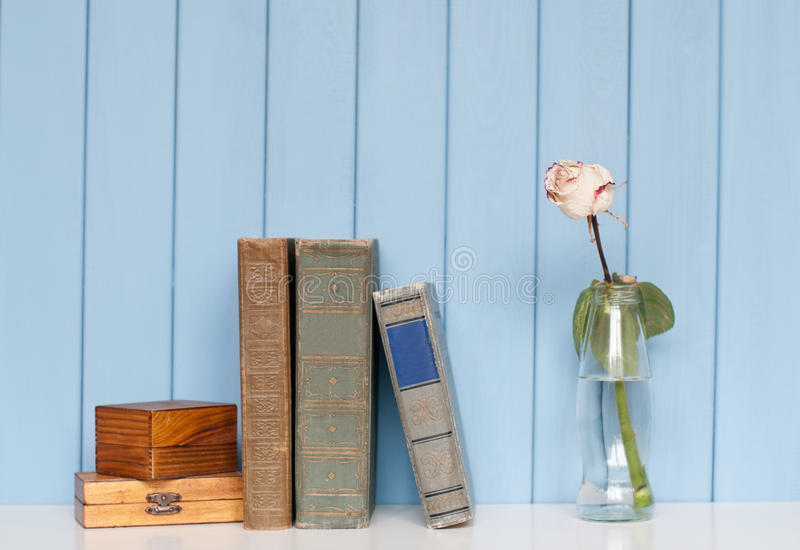 Books pile, two wooden boxes and white rose in the bottle. Ancient antiquarian books are stacked on home bookshelf with rose in the bottle of water and two royalty free stock images