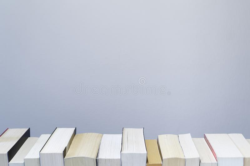 Books in a row on light grey background. Books in a row on the bottom of the picture with light grey background royalty free stock images