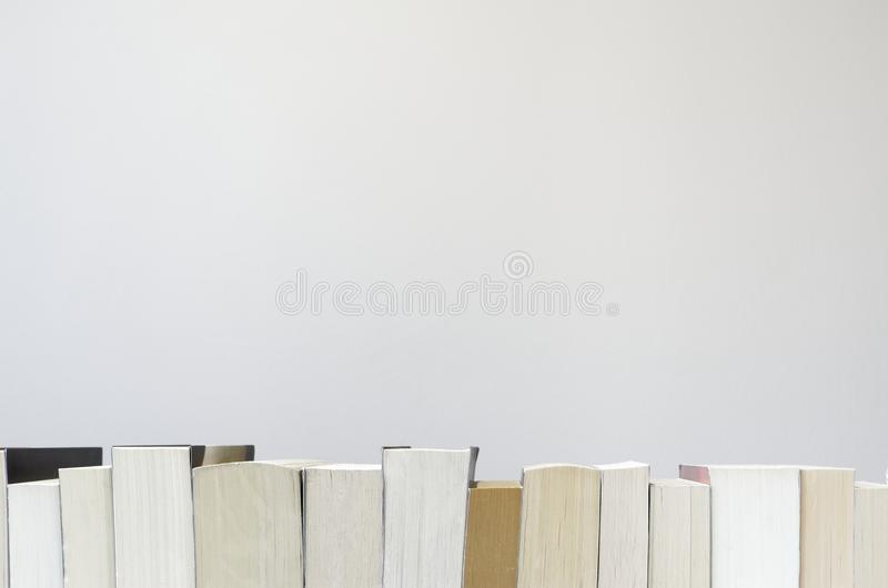 Books in a row on light grey background. Row of the books on bottom of a light grey background stock photo