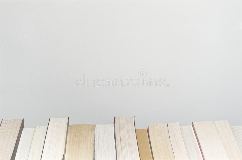 Books in a row on light grey background. Books in a row on the bottom with light grey background royalty free stock photography