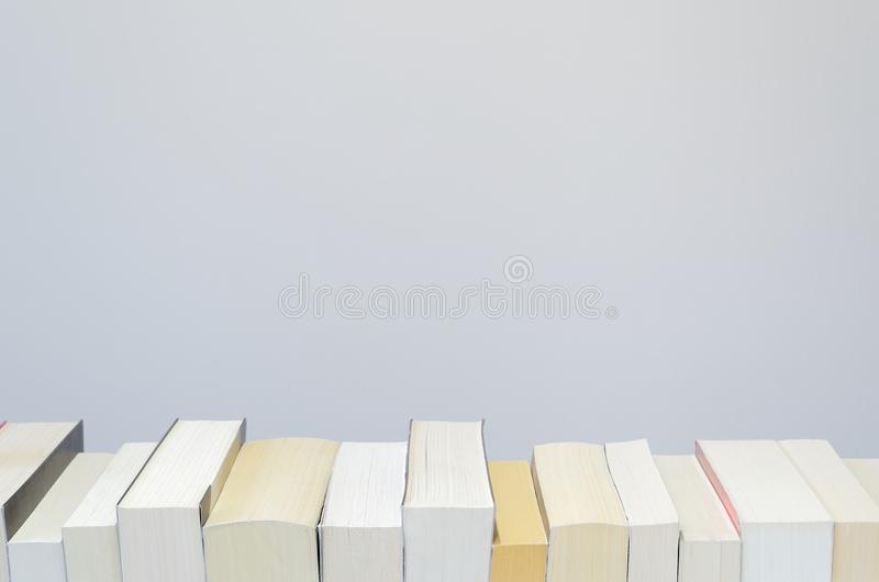 Books in a row on light grey background. Books in a row on the bottom of the photo and with light grey background stock photography