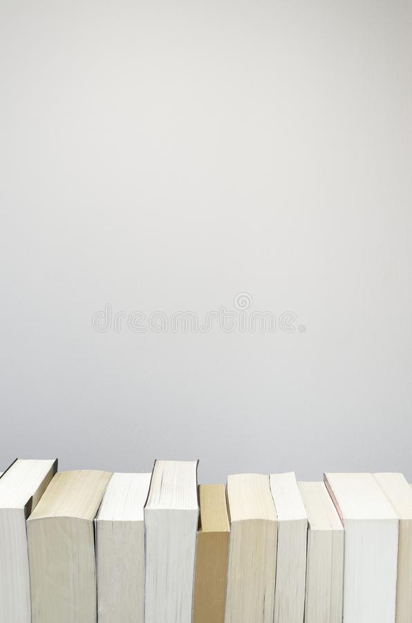 Books in a row on light grey background. Books in a row on the bottom of the picture with light grey background royalty free stock image