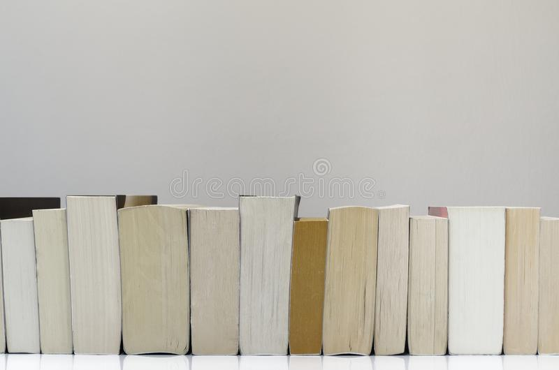 Books in a row on light grey background. Books in a row lying on white table with light grey background stock images