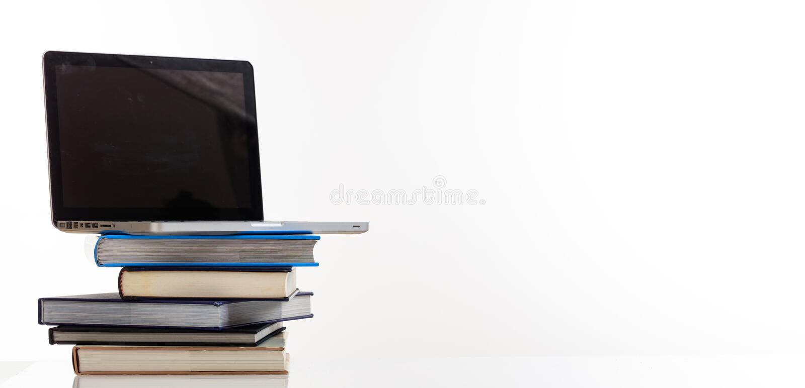 Books stack and a laptop on white background royalty free stock photo