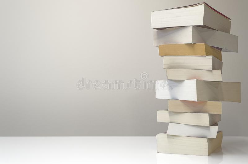 Pile of books on the table with light grey background. Books in stack on the right side of a table and with light grey background stock photo