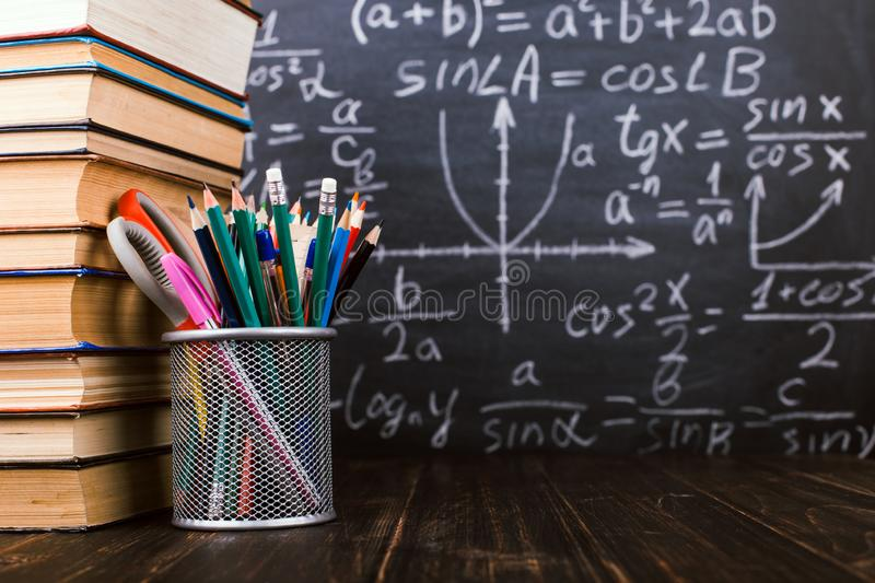 Books and stand for pens on a wooden table, against the background of a chalk board with formulas. Teacher`s day concept and back stock images