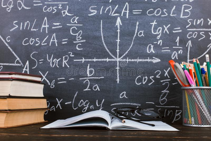 Books and stand for pens on a wooden table, against the background of a chalk board with formulas. Teacher`s day concept and back. Books and stand for pens on royalty free stock photos
